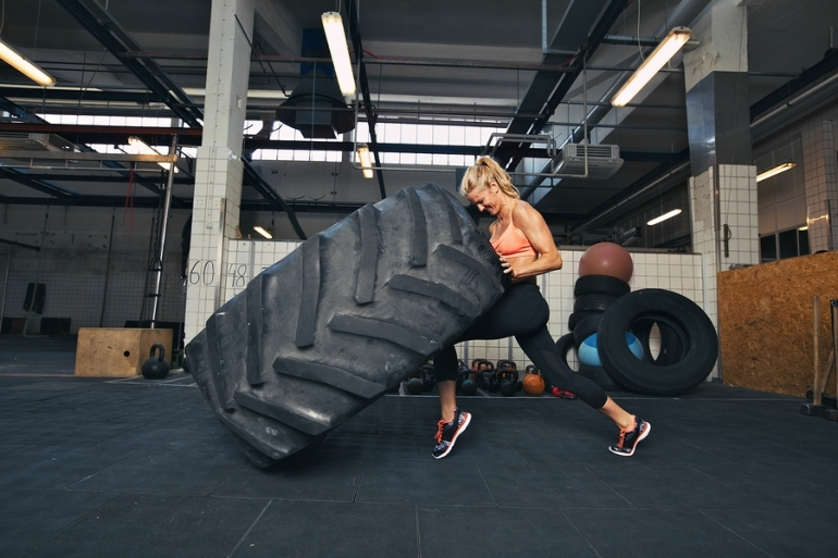 Woman Flipping A Huge Tire At Gym